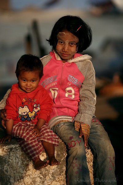 A young girl sits with her brother on the river bank.