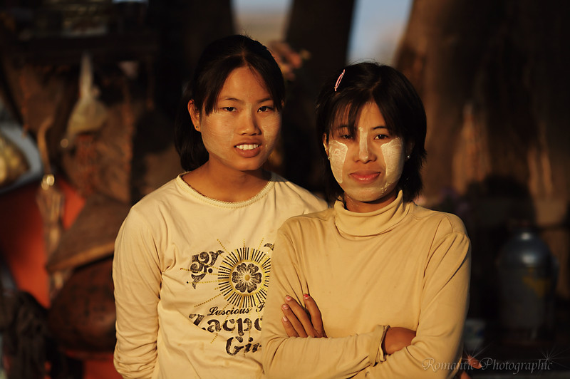 Two women from a small kiosk between the river bank and the road pose for a photo in the beautiful dawn light.