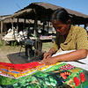 Sitting beneath an unforgiving sun, this woman uses an ancient sewing machine to stitch grain sacks.