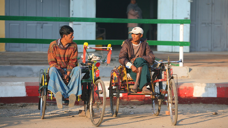 Trishaw taxis wait for customers outside the market.