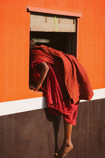 A monk climbs aboard the train using a most undignified method.