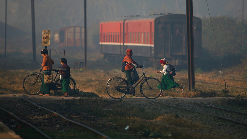 Children cross the tracks on their way to school in the morning.