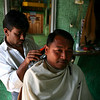 A barber diligently works on a customer.