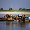 Gold miners systematically dredge the river bottom.