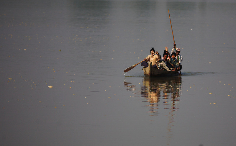 A small boat makes its way across the river to a small settlement on the bank.