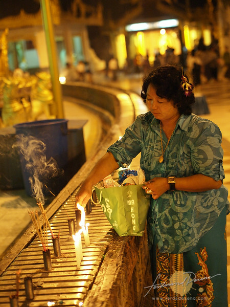 A Burmese lady lights up some candles at one of the stations