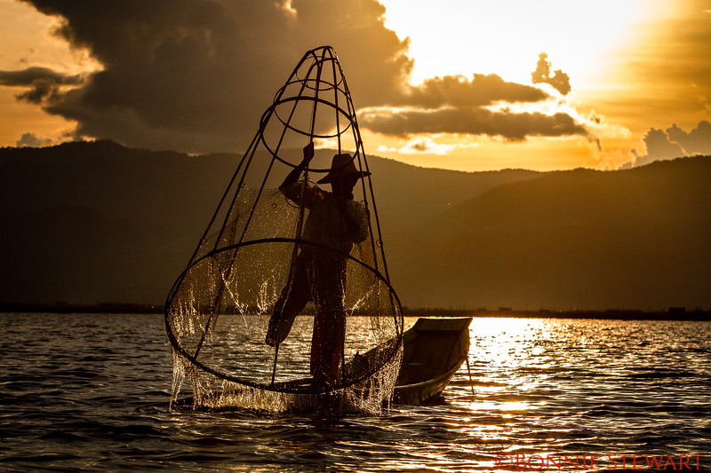 "Local fisherman at sunset demonstrating their famous ""leg rowing"" and fishing technique using the mesh cone to capture fish"