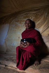 Monk at the Shinbinthalyaung reclining Buddha next to the Shwesandaw Pagoda
