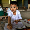 "Young boy studies.  The substance on his face is for sun protection and ""beauty"".  Most Burmese use this type of sun protection."
