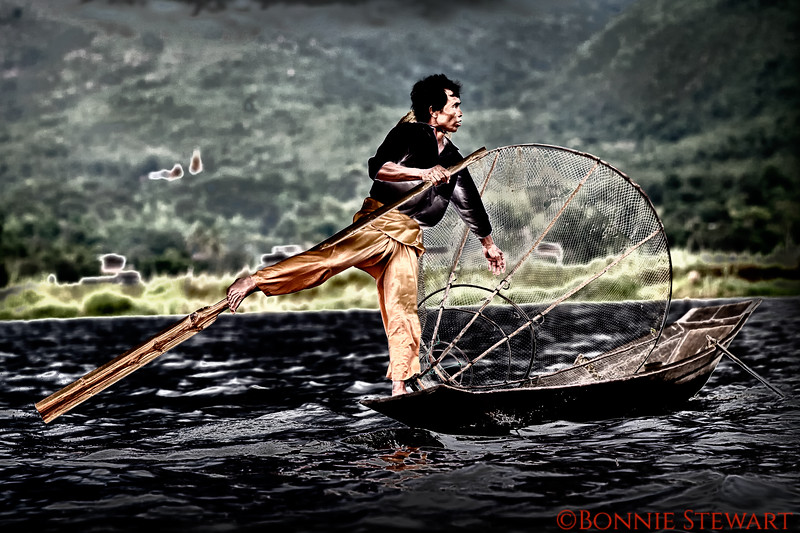 """Local fisherman at sunset demonstrating their famous """"leg rowing"""" and fishing technique using the mesh cone to capture fish"""