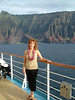 Ann on deck with Na Pali Coast in foreground.
