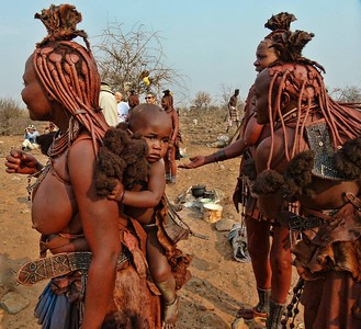 Himba women apply otjize, a paste of butter, fat and red ochre each morning to their skin and hair, giving them a distinctive red hue.