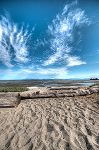 Driftwood, low tide, and big sky. This is an HDR redo.