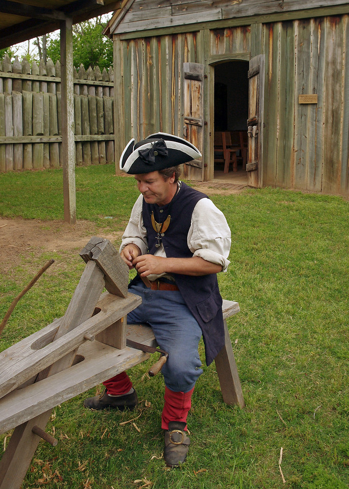A French soldier demonstrates how to use a shaving horse; Fort St. Jean Baptiste State Historic Site, Natchitoches, Louisiana.