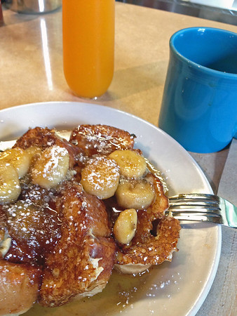 Cinnamon french toast with bananas and pure maple syrup, fresh orange juice and coffee at Tasi Cafe.