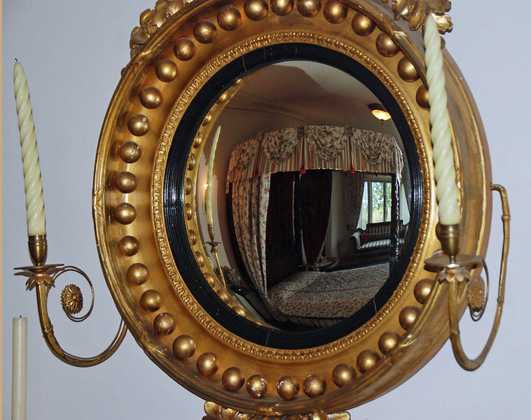 A convex mirror over a fireplace mantle displays the whole bedroom.