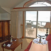 The deck overlooks the Pacific Ocean.  A flat-screen TV and DVD player is housed in the cabinet.