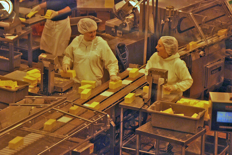 These workers are adding or subtracting small slices of cheddar cheese so that the weight of each package is correct.  Reminded me of Lucy Ricardo.