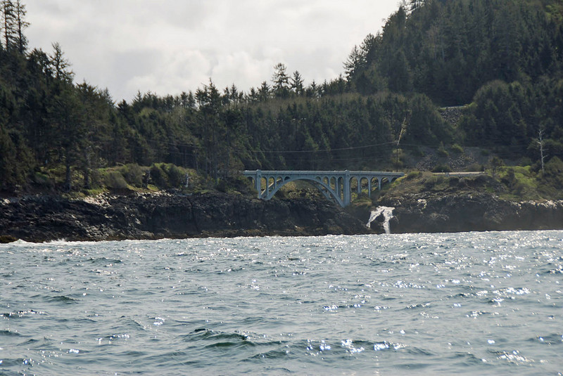 A bridge along the Oregon coast.  Notice the waterfall on the right side of the bridge.
