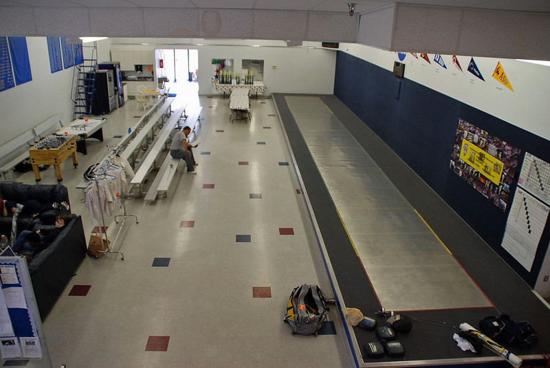 The raised finals strip at the Northwest Fencing Center with bleachers for the spectators.  There's a video system and monitors for instant replay.  A tv lounge is on the left, foosball table behind the bleachers and a small kitchen at the rear.