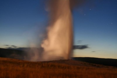 Old Faithful Geyser eruption by night.