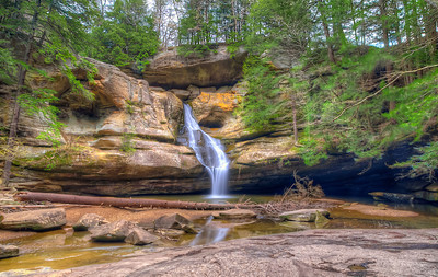 Cedar Falls is among the most magnificent waterfalls in Ohio and certainly one of the most popular in the Hocking Hills. No matter what time of year you visit, Cedar Falls Ohio is a sight to behold. In autumn, a trip to Cedar Falls is accentuated by fall foliage, and in winter, the 50-foot waterfall turns into a stream of icicles. When the snows of winter melt in springtime, Cedar Falls begins flowing at full capacity. It is said to be the largest waterfall in the Hocking Hills by volume. The name Cedar Falls is a misnomer — the result of mistaken identity. Early settlers to the area misidentified the stately hemlock trees as cedar trees; consequently, this park was incorrectly named. Despite the mistake, the name Cedar Falls has been used ever since.  Equipment=Nikon D7000 Lens Used=Tamron SP AF 10-24mm F/3.5-4.5 Lens Exposures=3 Location=Logan Ohio  Workflow= PhotoMatix 4.2 Adobe PhotoShop Cs6(Lightning Adjustments=-2) Adobe Light room 4.1 Software, Nik Color Efex=Glamor Glow, Brilliance/Warmth, Detail Extractor, Foliage, and Tonal Contrast{Colors Only)  Nik Sharpener Pro 3.0