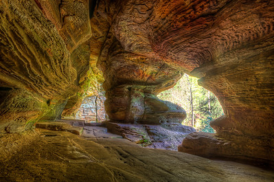 Rock House is unique in the Hocking Hills' region, as it is the only true cave in the park. It is a tunnel-like corridor situated midway up a 150-foot cliff of Blackhand sandstone.  This House of Rock has a ceiling 25 feet high while the main corridor is 200 feet long and 20 to 30 feet wide. The cavern was eroded out of the middle zone of the Blackhand sandstone. The resistant upper zone forms the roof and the lower zone forms the floor. Water leaking through a horizontal joint running parallel to the cliff face caused the hollowing of the corridor. This main joint or crack is very visible in the ceiling of the Rock House. A small series of joints run north to south at right angles to the main joint. Enlargement of this series of joints formed the window-like openings of Rock House.  Nature has hewn out of this cliff the Rock House complete with seven Gothic-arched windows and great sandstone columns which bear its massive roof. As one might imagine, Rock house was used for shelter by past visitors. Hominy holes, small recesses in the rear wall of Rock House, served as baking ovens for Native Americans using the cave. By building a fire in the small recesses, the rock became heated on all sides, and food could be bakes in this crude manner. Further evidence of past use is the presence of chiseled out troughs or holding tanks found in the stone floor. When rainfall is abundant, springs of water permeate through the porous sandstone and flow into these troughs fashioned by man and, when full, continue across the floor and out of the windows. In this way, residents were able to maintain a small water supply in Rock House. According to local folklore, other not so welcome visitors frequented Rock House. Robbers, horse thieves, murderers and even bootleggers earned Rock House its reputation as Robbers Roost.  Equipment=Nikon D7000 Lens Used=Tamron SP AF 10-24mm F/3.5-4.5 Lens Exposures=7 Location=Logan Ohio  Workflow= PhotoMatix 4.2 Adobe PhotoShop Cs6(Lightning Adjustments=-2) Adobe Light room 4.1 Software, Nik Color Efex=Glamor Glow, and Brilliance/Warmth Topaz Adjust 5=Photo Pop