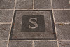 "An ""S"" inset in front of the front doorway."