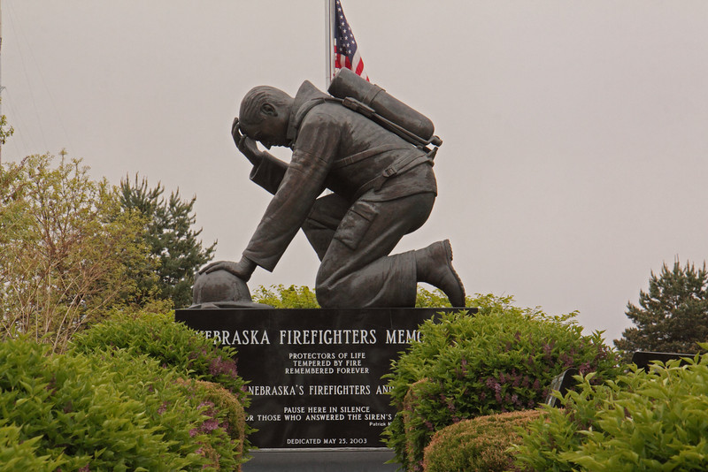 The Nebraska Firefighters Memorial is a large bronze figure of a kneeling firefighter sculpted by S. Mariami in 2001 (dedicated 2003).