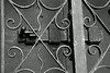 Black/white study of the lock and fancy grillwork of the front door.