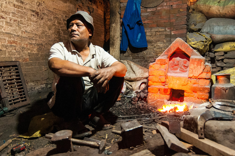 A blacksmith beats out a living in the backstreets of Bhaktapur. Nepal