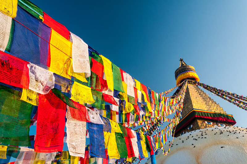 Prayer flags strung from the top of the stupa flutter in the breeze. Boudha. Nepal
