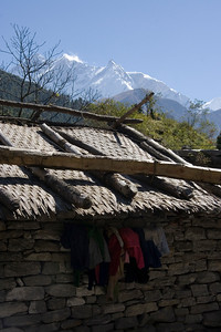 Lanudry dries under a roof with the Annapurna range to the east