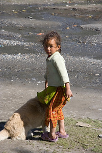 Girl taking a dog for a walk by the windy river bank