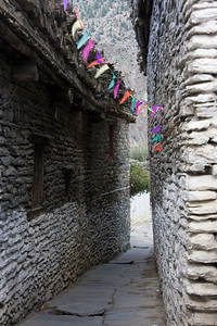 Flags add color to an otherwise gray alley in Marpha village
