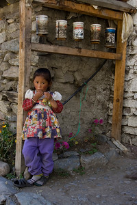 Girl standing next to makeshift prayer wheels in Manang