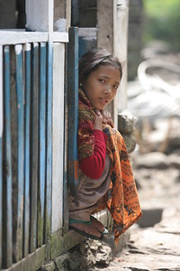 Young girl watching children play in the village street