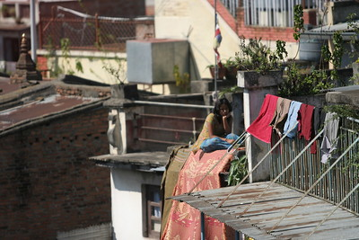 Girl sitting on rooftop, Kathmandu. What she looking at?