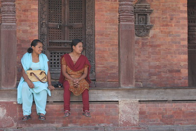 Women at Durbar Square in Kathmandu. they are looking at the man sleeping.