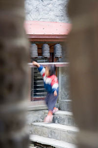 A girl spinning a prayer wheel in the Marpha Monastery