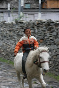 Young boy riding a horse through Chame