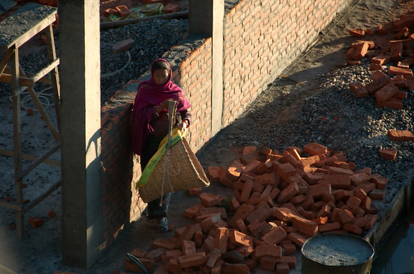 Woman portering bricks to building site at first light, Nagarkot, 26 November 2007