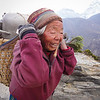 Sherpa woman transporting goods above Dingboche, Nepal