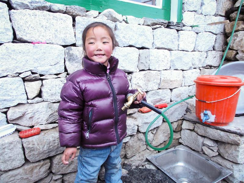 Girl filling water bottles in Dingboche, Nepal