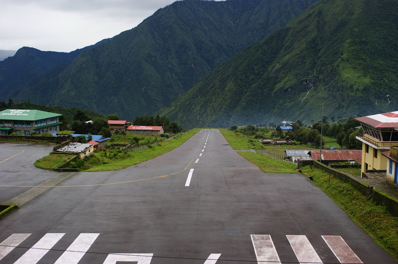 Lukla airport main runway.  You may not get a full sense of the perspective from this photo, so I'll explain.  The first 50 yds or so are flat.  Then the runway slopes downhill at about 10 degrees till it suddenly plunges into empty space at the end.  Landing is exciting. Taking off is sheer exhilaration - the plane turns at the very top of the runway to get all the distance it can.  Then the engines rev and strain against the brakes.  Finally the pilot releases the brakes and you hurtle down the slope as if it were a ski jump.  The plane lifts off just before it runs out of tarmac (and ground) altogether.  Then the wheels retract with a loud bang, and suddenly you are floating hundreds of metres over the deep gorge below.