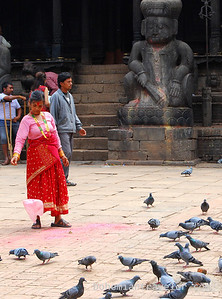 Woman feeding pigeons in Tachupal Tole.
