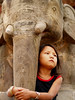 Sad girl in Kirtipur under a tipical stone elephant in the temples of Nepal