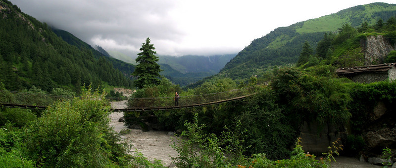 Suspension bridge in the Annapurnas trek, surrounded by lush foliage
