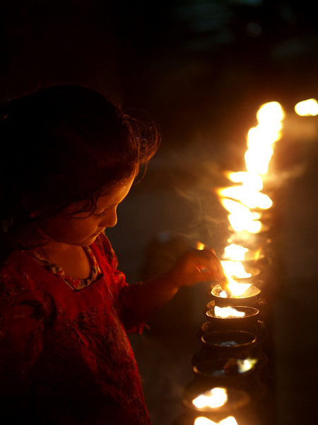 Little child lighting a candel in a temple of Patan