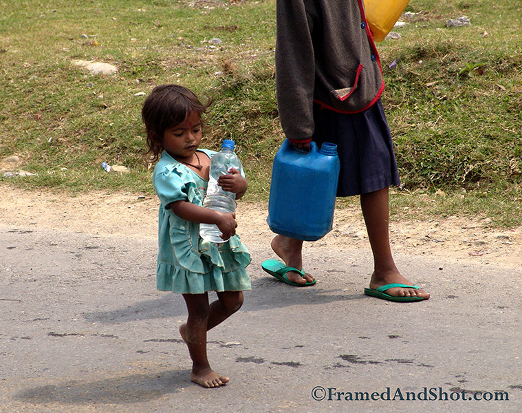 """<strong><center>The Water Carrier<br> Water is a key component in determining the quality of our lives. It is more important than oil and gold - and in some areas they learn at an early age the importance of saving and caring for their supply. This photo is taken in <a href=""""http://en.wikipedia.org/wiki/Pokhara"""" target=""""_blank""""><span style=""""color: #0080ff;"""">Pokhara</span></a>, in Nepal. It is a remarkable place of natural beauty, situated at an altitude of 827m from the sea level and  200km west of The Kathmandu valley.  This little girl had her chores, carrying water for the family, she stands in our memory as the reminder of water conservation and how we take resources  for granted in our part of the world. It would help her, and many others like her, if you would reduce your resource usage.  <span style=""""color: #333333;"""">.</span>"""